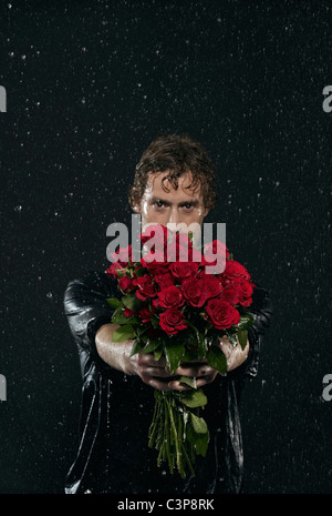 Man holding bunch of flowers, standing in rain. - Stock Photo