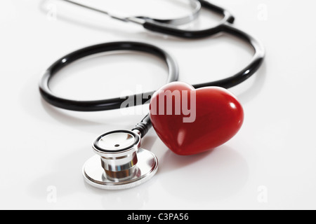 Stethoscope with heart shape object on white background, close up - Stock Photo