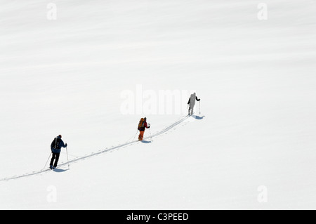 A roped up group of ski tourers breaking a trail on the Haute Route ski tour, Switzerland. - Stock Photo