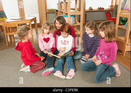 Germany, Female nursery teacher and children in nursery - Stock Photo