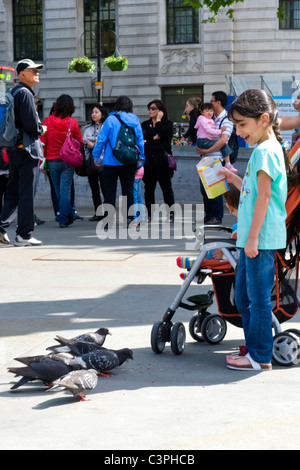 London , Westminster , Trafalgar Square , family , mother in hijab & three young children , 1 in pushchair , feed - Stock Photo