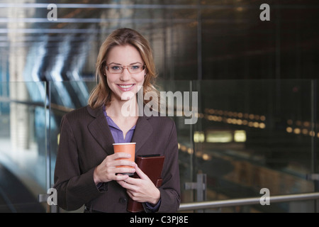 Germany, Bavaria, Munich, Business woman at subway station holding paper cup, smiling, portrait - Stock Photo