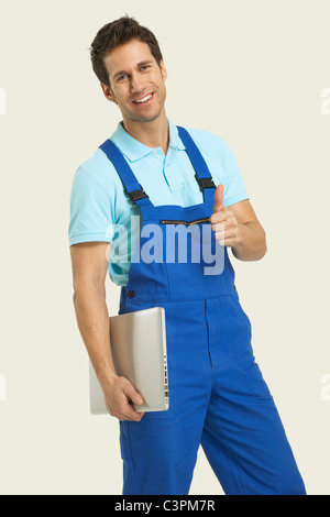 Man in overall holding laptop and showing thumbs up sign, portrait - Stock Photo