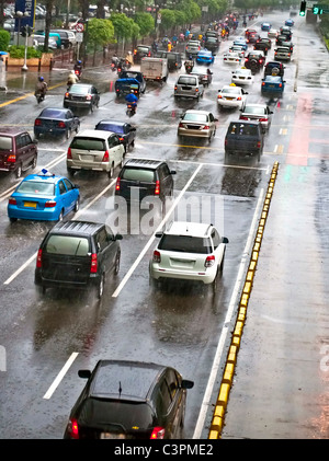 Crowded traffic jam in urban street in bad weather - Stock Photo