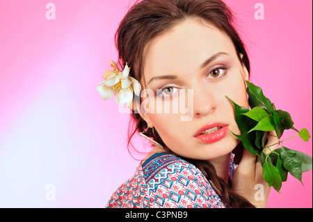 Portrait of a beautiful young girl in Asian clothing, holding a plant next to her face. Pink and white background. - Stock Photo