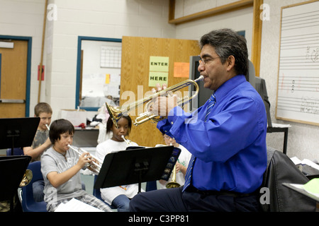 Male orchestra teaching playing trumpet leads multi-ethnic group of students trumpeters during orchestra class at - Stock Photo