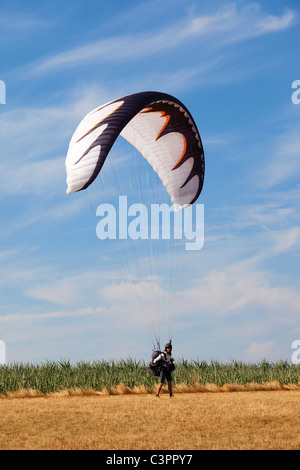 Germany, Moselle, Person parachuting landing on landscape - Stock Photo