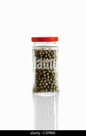 Green peppercorns in glass jar, close up - Stock Photo