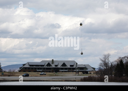 Helicopter airlifts supplies from the Appalachian Mountain Club Highland Center in the White Mountains, New Hampshire - Stock Photo