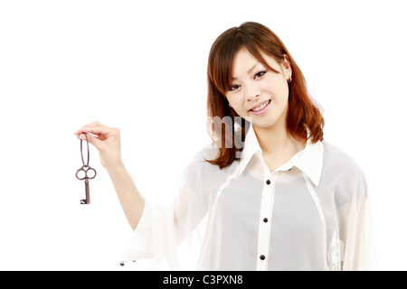 Beautiful Japanese woman holding a old key in her hand - Stock Photo