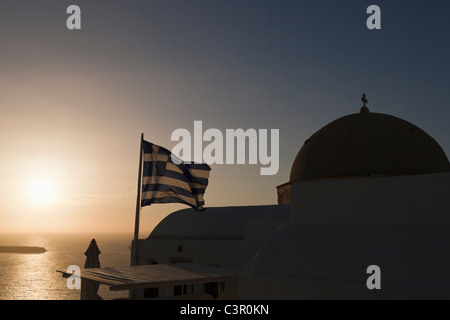 Europe, Greece, Aegean Sea, Cyclades, Thira, Santorini, Oia, Greek flag beside the cupola of a churc - Stock Photo