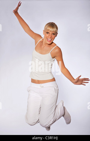 Young woman jumping against gray background, smiling, portrait - Stock Photo