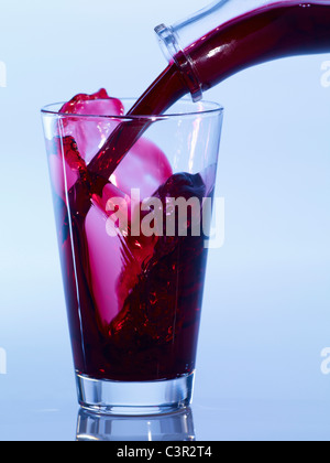 Pouring black currant juice in glass, close-up - Stock Photo