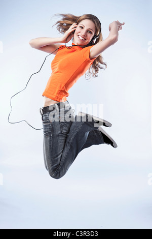 Young woman wearing headphones, jumping in air - Stock Photo