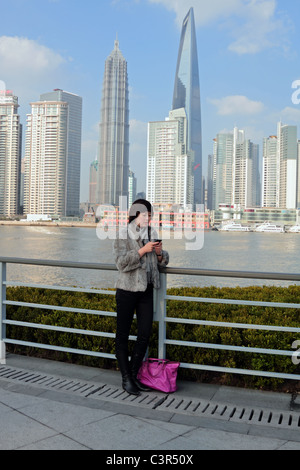 Model released Chinese woman using iPhone with Pudong skyscrapers including the World Financial Center in the background - Stock Photo