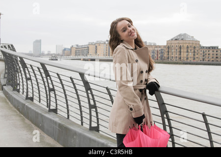 Young woman with umbrella by river - Stock Photo