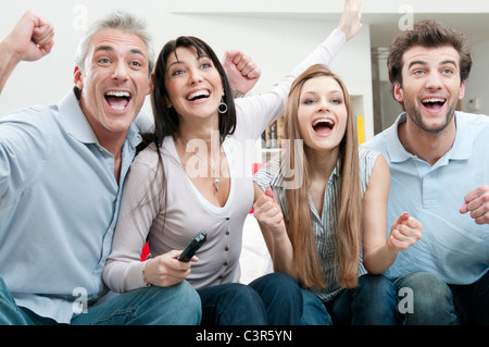 Excited friends watching sport on TV - Stock Photo