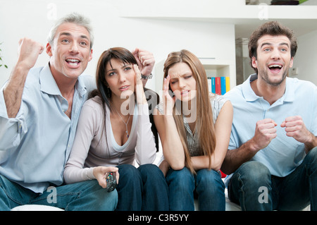 Excitement and boredom at TV - Stock Photo
