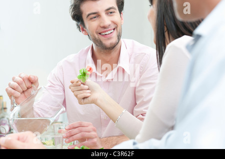 Smiling man pouring fresh water in glass - Stock Photo