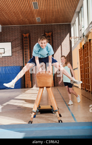Germany, Emmering, Boy (12-13)  jumping with girl standing in background - Stock Photo