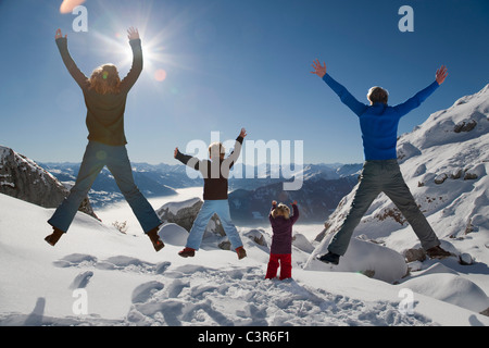 Happy family jumps in winter mountains - Stock Photo