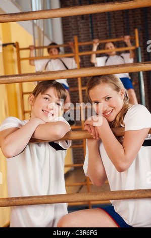 Germany, Emmering, Girls on wall bars with boys in background - Stock Photo