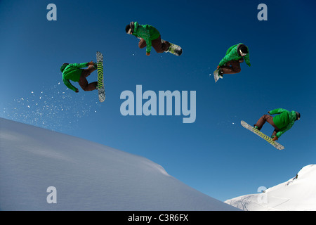 Snowboarder dangerous free ride jump - Stock Photo