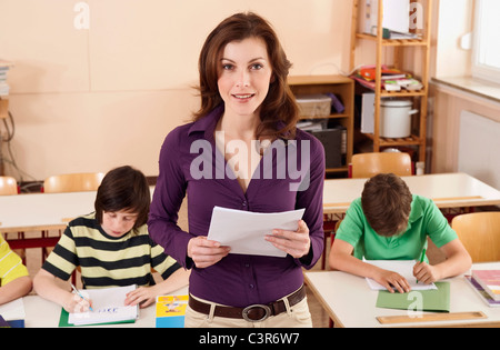Germany, Emmering, Teacher smiling with students writing in background - Stock Photo
