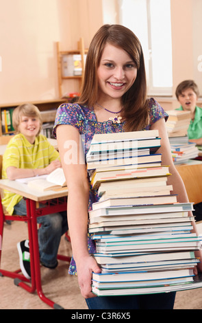 Germany, Emmering, Girl (12-13) holding stack of books with boys smiling in background - Stock Photo