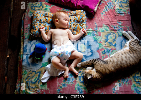 Thailand, Baby and cat sleeping on bed - Stock Photo