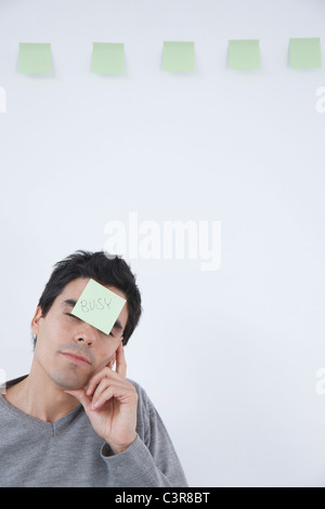 Man with 'busy' post-it note on his head - Stock Photo