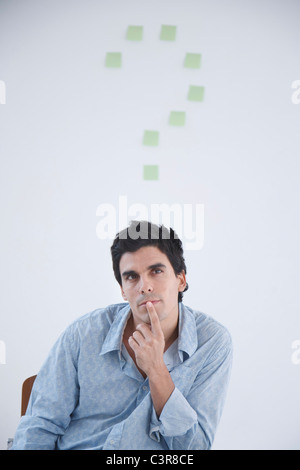 Man thinking with post-it note question makr behind him - Stock Photo