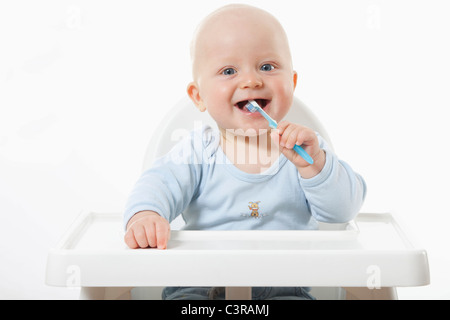 Baby boy (6- 11 Months) brushing teeth, smiling, portrait - Stock Photo