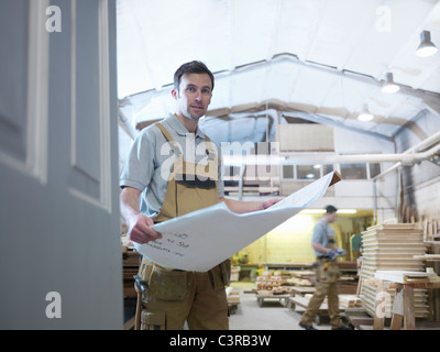 Woodworker with plans in workshop - Stock Photo