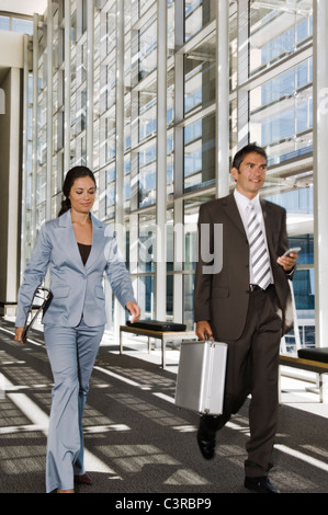 Business people walking down a corridor - Stock Photo