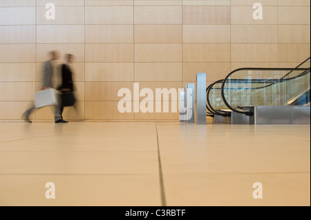 Business people walking towards an escalator - Stock Photo