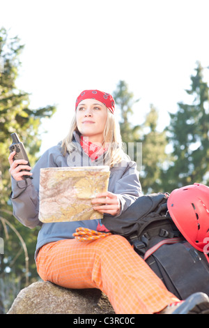 Active young woman backpack search navigation map rock climbing - Stock Photo