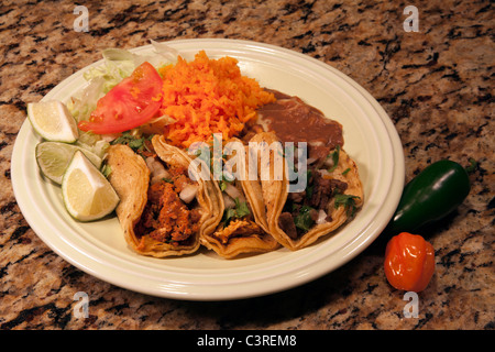 Plate of three tacos with rice and beans - Stock Photo