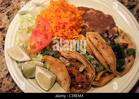 Plate of three tacos with rice and beans USA - Stock Photo