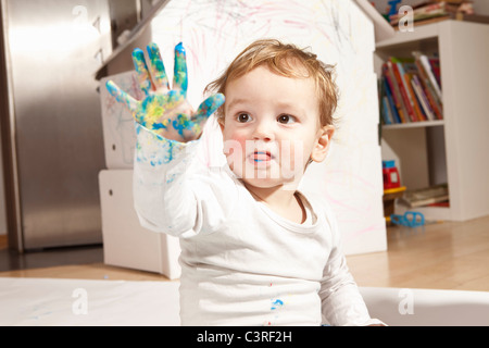 Boys hand covered with finger paint - Stock Photo