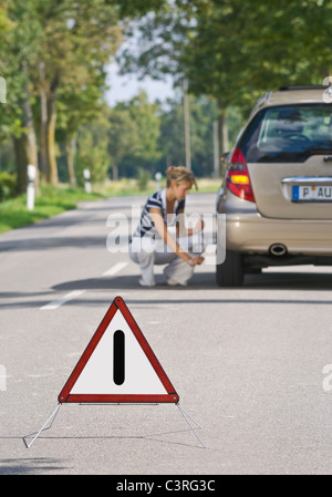 Germany, Augsburg, Young woman repairing puncture - Stock Photo