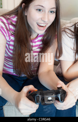 teenage girl playing a video game - Stock Photo