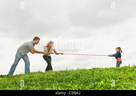 Germany, Cologne, Parents playing tug of war with girl (2-3 Years) - Stock Photo