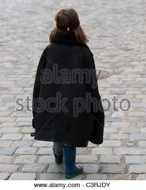 Boy Child toddler rear view walking wearing fathers sheepskin jacket - Stock Photo