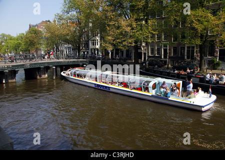 TOURIST BOAT ON CANAL & BRIDGE AMSTERDAM HOLLAND 24 April 2011 - Stock Photo