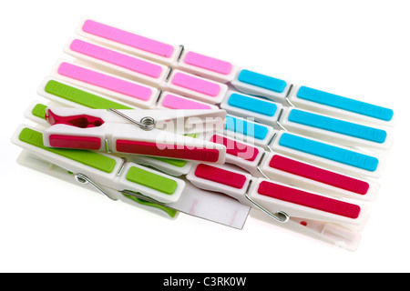 Pile of coloured plastic clothes pegs clipped onto cardboard - Stock Photo