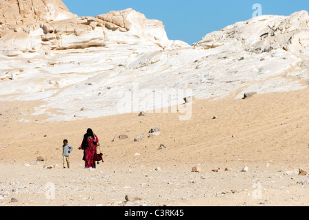 Bedouin woman with child walking in the desert - Sinai Peninsula, Egypt - Stock Photo
