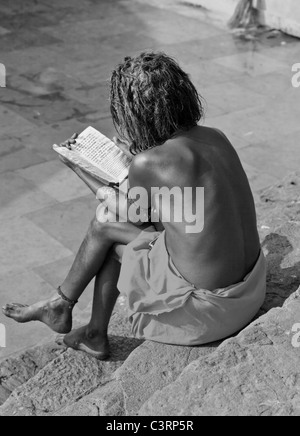 Sadhu studying the Veda in a temple in Guwahati, Assam, India - Stock Photo