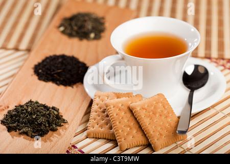 A cup of tea near three piles of various kinds of tea - Stock Photo