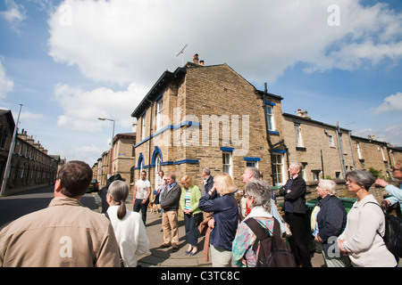 A tour group learn about the workers houses near Salts mill in Saltaire, Yorkshire, UK. - Stock Photo